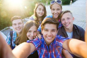 group of teenagers in the park do selfie
