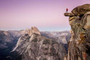 Man on overhanging rock at Glacier Point, Yosemite National Park, California, USA